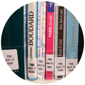 """vignette ronde du projet """"fausses cotes"""" où l'on voit les tranches de livres rangés dans une bibliothèque, à cliquer sur le site de cécile briand"""