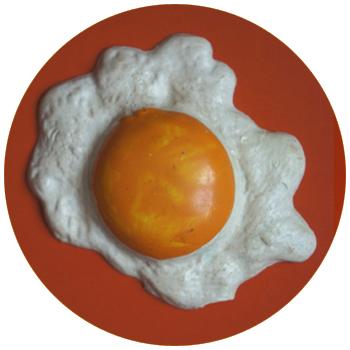 """vignette ronde du projet """"souvenirs"""" où l'on voit un œuf au plat en plastique, à cliquer sur le site de cécile briand"""